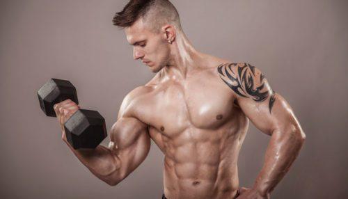 Homem exibindo sua hipertrofia muscular com um halter.