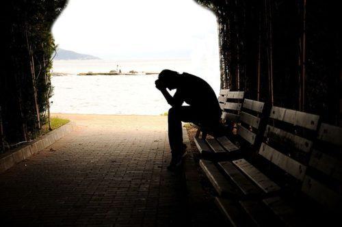 Homem triste e desolado sentado em um banco na rua.
