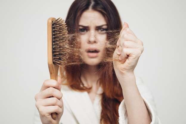Mulher se espanta com a queda de cabelo.