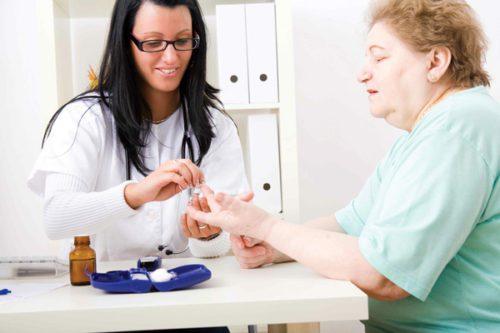 Doutora aferindo o nível de glicose do diabético.
