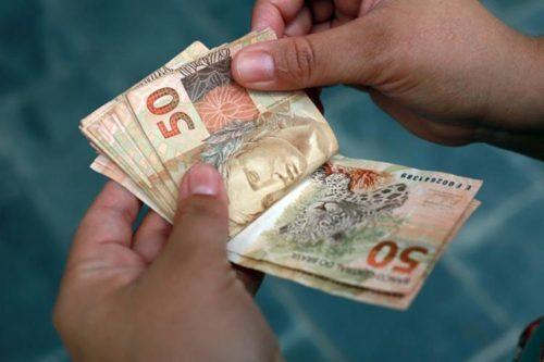 homem contando varias notas de R$ 50 (cinquenta reais)