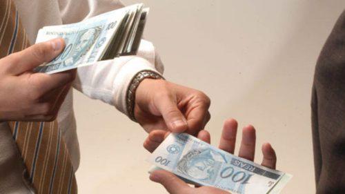 homem emprestando notas de R$ 100 (cem reais)