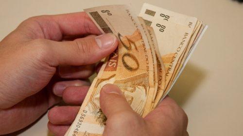 homem contando notas de R$ 50 reais (cinquenta reais)