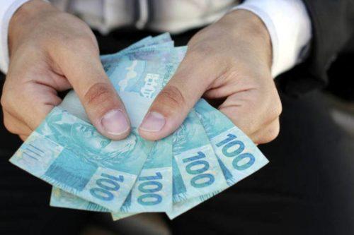 homem contando notas de R$ 100 (cem reais)
