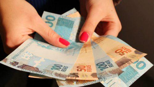 mulher contando notas de R$ 100 e R$ 50 (cem e cinquenta reais)