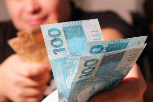 homem emprestando varias notas de R$ 100 (cem reais)