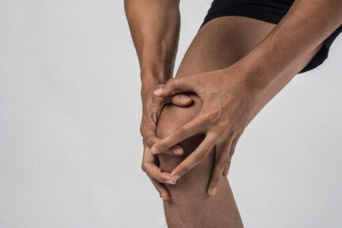 Atleta com dores no joelho após treino intenso.
