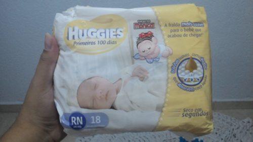 Mãe segura fraldas Huggies para Recém Nascido