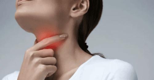 Mulher com a mão na garganta por estar com inflamação