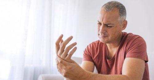 homem expressa bastante dor nas mãos, em vista da tendinite