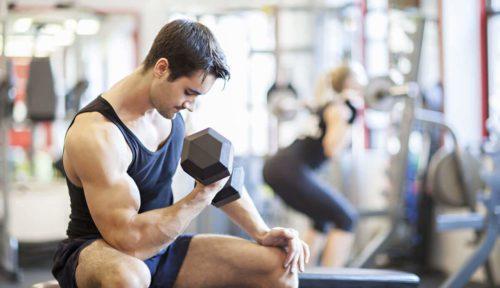 Homem treinando bíceps na academia.