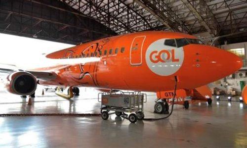 Avião da GOL laranja parado no Hangar do aeroporto.