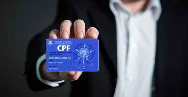 Homem de terno exibe seu CPF para consulta