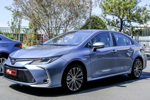 Novo Toyota Corolla híbrido estacionando proximo a praça.